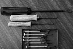 Insieme dei cacciaviti grigi su una tavola grigia fotografie stock