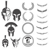 Insieme dei caschi dei guerrieri e degli elementi spartani di progettazione per l'emblema illustrazione di stock