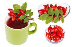 Insieme dei cinorrodi sulla tazza con tè caldo ed in ciotole di vetro Canina del Rosa Immagini Stock Libere da Diritti
