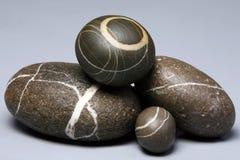 Insieme dei ciottoli a strisce delle rocce su fondo grigio Immagini Stock Libere da Diritti