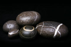Insieme dei ciottoli a strisce delle rocce su fondo nero Fotografia Stock Libera da Diritti