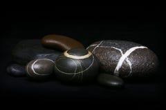 Insieme dei ciottoli a strisce delle rocce su fondo nero Immagine Stock