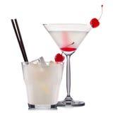 Insieme dei cocktail bianchi con la ciliegia e la paglia nera isolate su fondo bianco Fotografia Stock