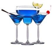 Insieme dei cocktail blu con la decorazione dai frutti e dalla paglia variopinta isolati su fondo bianco Fotografie Stock Libere da Diritti