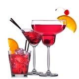 Insieme dei cocktail rossi con la decorazione dai frutti e dalla paglia variopinta isolati su fondo bianco Fotografia Stock Libera da Diritti