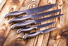 Insieme dei coltelli da cucina brillanti del metallo su una tavola di legno Fotografie Stock