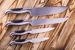 Insieme dei coltelli da cucina brillanti del metallo su una tavola di legno Fotografia Stock