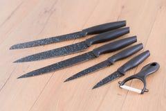 Insieme dei coltelli da cucina su un tagliere di legno Fotografia Stock