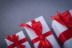 Insieme dei contenitori di regalo avvolti sul concetto di feste della superficie di grey Immagine Stock