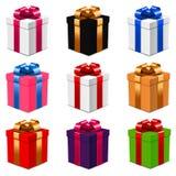 Insieme dei contenitori di regalo con gli archi in vari colori su bianco Fotografia Stock