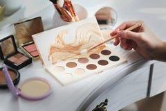 Insieme dei cosmetici decorativi sul boudoir immagini stock
