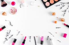 Insieme dei cosmetici per le donne con il modello bianco di vista superiore del fondo della lavanda Immagini Stock