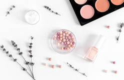 Insieme dei cosmetici per le donne con la vista superiore del fondo bianco della lavanda Fotografia Stock