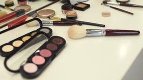 Insieme dei cosmetici per trucco su una tavola bianca archivi video
