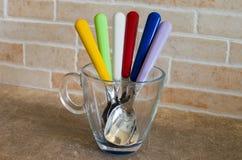 Insieme dei cucchiai colorati in una tazza fotografia stock