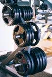 Insieme dei dischi dei bilancieri del metallo sul supporto del bilanciere nella palestra di forma fisica Fotografia Stock Libera da Diritti