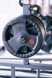 Insieme dei dischi dei bilancieri del metallo sul supporto del bilanciere nella palestra di forma fisica Immagine Stock
