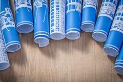 Insieme dei disegni di ingegneria rotolati blu sul constructi di legno del bordo Fotografia Stock