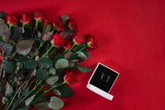 Insieme dei gioielli degli orecchini dorati in un contenitore e nelle rose rosse di regalo su Re Immagini Stock Libere da Diritti