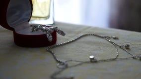 Insieme dei gioielli dell'anello dorato in contenitore di regalo, orecchini, collana con le perle ed accessori della decorazione video d archivio