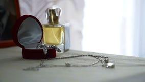 Insieme dei gioielli dell'anello dorato nel contenitore di regalo, in orecchini, in collana con le perle e nei profumi degli acce archivi video