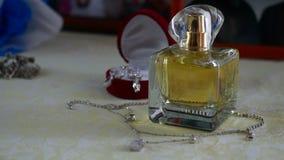 Insieme dei gioielli dell'anello dorato nel contenitore di regalo, in orecchini, in collana con le perle e nei profumi degli acce video d archivio
