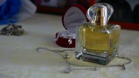 Insieme dei gioielli dell'anello dorato nel contenitore di regalo, in orecchini, in collana con le perle e nei profumi di nozze d video d archivio