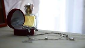 Insieme dei gioielli dell'anello dorato in un contenitore di regalo, in orecchini, in collana con le perle e nei profumi degli ac archivi video