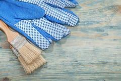 Insieme dei guanti di sicurezza dei pennelli sulla costruzione c del bordo di legno Fotografie Stock