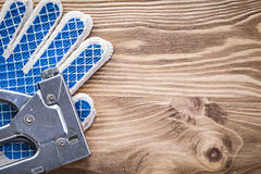 Insieme dei guanti protettivi della pistola della graffetta sul bordo di legno Immagine Stock Libera da Diritti