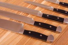 Insieme dei knifes della cucina su priorità bassa di legno Immagini Stock