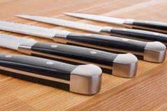 Insieme dei knifes della cucina su priorità bassa di legno Fotografia Stock