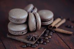 Insieme dei maccheroni francesi differenti dei biscotti con i chicchi di caffè su fondo di legno closeup Caffè, gusti del cioccol fotografie stock