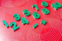 Insieme dei numeri alla scuola, attrezzatura per istruzione Strumenti per imparare numeri verdi su un fondo rosso Istruzione e fotografie stock