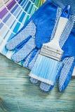Insieme dei pennelli della tavolozza di colore dei guanti di sicurezza sul bordo di legno Immagini Stock