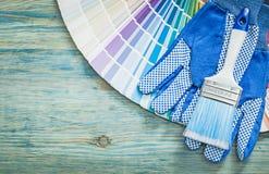 Insieme dei pennelli della tavolozza di colore dei guanti protettivi sulla b di legno Fotografie Stock