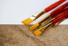 Insieme dei pennelli dorati della setola sul fondo bianco e strutturato del cemento con lo spazio della copia Fotografie Stock Libere da Diritti