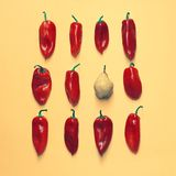 Insieme dei peperoni luminosi ordinatamente sistemati e di una pera su un fondo giallo Fotografia Stock