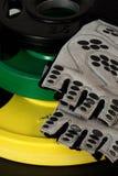 Insieme dei pesi variopinti del disco e dei guanti di allenamento Immagini Stock