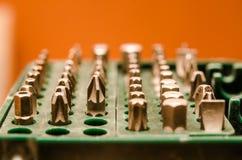 Insieme dei pezzi per il cacciavite in una cassa verde su un backgrou arancio immagine stock