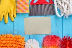 Insieme dei rifornimenti di pulizia sulla tavola di legno immagine stock libera da diritti
