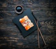 Insieme dei rotoli di sushi con soia ed i bastoncini Immagini Stock