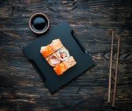 Insieme dei rotoli di sushi con soia ed i bastoncini Fotografie Stock Libere da Diritti