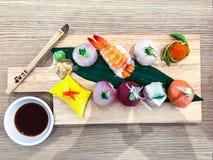 Insieme dei sushi e dei rotoli differenti sul bordo di legno Immagine Stock