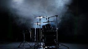 Insieme dei tamburi, dei piatti e di altri strumenti di percussione Fondo fumoso nero stock footage