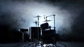 Insieme dei tamburi, dei piatti e di altri strumenti di percussione Fondo fumoso nero Indicatore luminoso posteriore archivi video