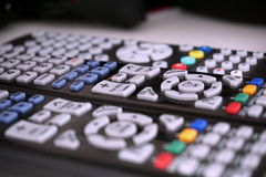 Insieme dei telecomandi neri con i bottoni variopinti sulla superficie di bianco come simbolo di home entertainment quando guarda Fotografia Stock Libera da Diritti