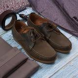 Insieme dei vestiti alla moda maschii su fondo di legno Immagine Stock