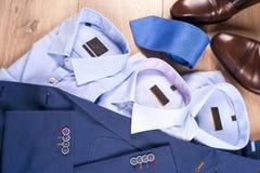 Insieme dei vestiti degli uomini classici - vestito blu, camice, scarpe marroni, cinghia e legame su fondo di legno Fotografie Stock