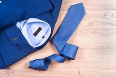 Insieme dei vestiti degli uomini classici - vestito blu, camice, scarpe marroni, cinghia e legame su fondo di legno Fotografie Stock Libere da Diritti